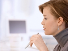 Side profile of woman holding a pen