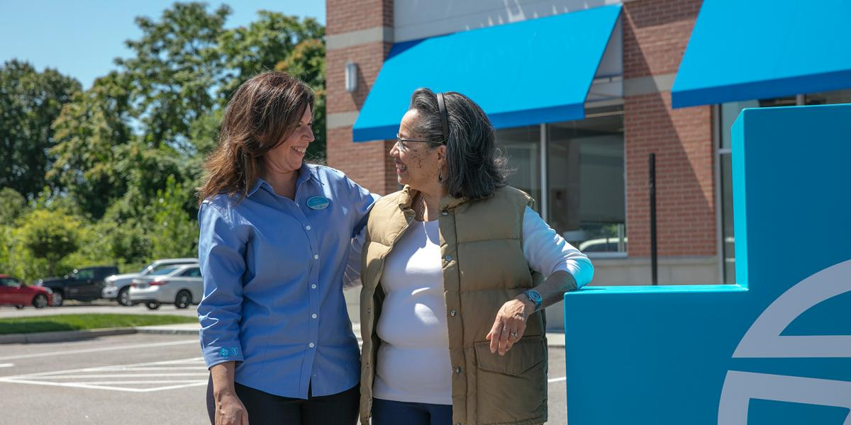 Melanie Teixeira, front desk receptionist at the East Providence Your Blue Store, talks with Muriel Jobbers, a BCBSRI customer.